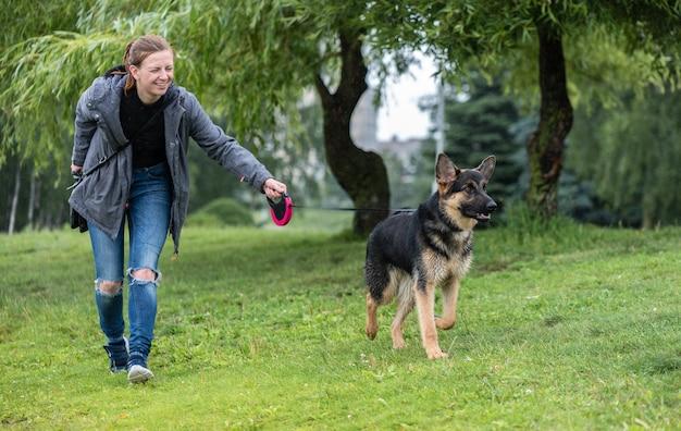 Ein mädchen geht mit einem schäferhund im park spazieren