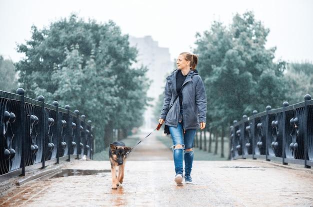 Ein mädchen geht mit einem schäferhund über eine brücke