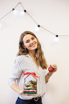 Ein mädchen hält eine florariumov, glasform mit sukkulenten, steinen und sand, verziert mit weihnachtsbändern. weihnachtsgeschenke für zu hause und im büro.