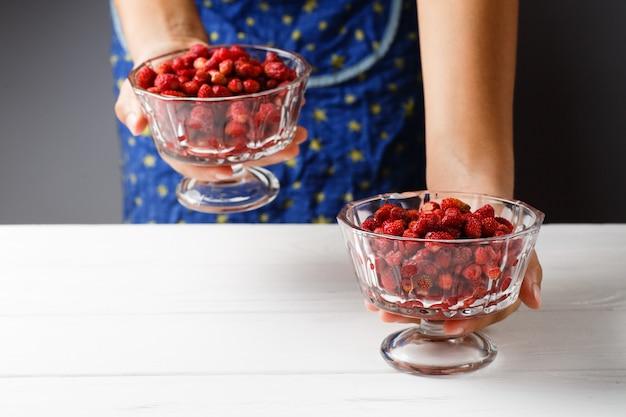 Ein mädchen hält eine glasschüssel mit reifen roten erdbeeren. nahansicht.