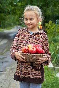 Ein mädchen hält einen weidenkorb voller roter äpfel