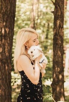 Ein mädchen hält im sommer ein weißes kaninchen in den armen in der natur