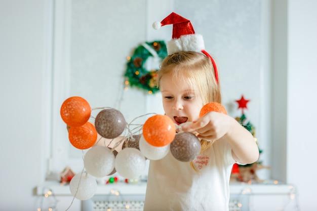 Ein mädchen hängt zu weihnachten eine girlande auf.