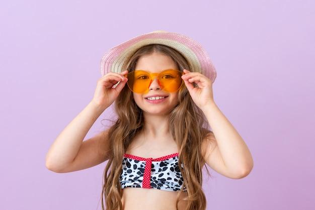 Ein mädchen im badeanzug setzt eine orangefarbene sonnenbrille auf.