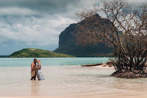 Ein mädchen im badeanzug und ein mann in shorts stehen im meer vor dem hintergrund des berges le morne auf der insel mauritius.