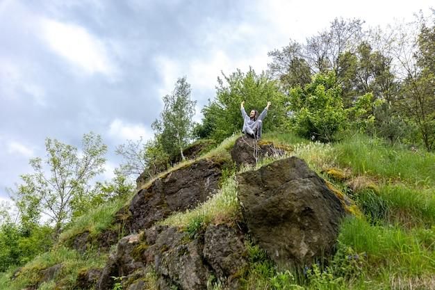 Ein mädchen im frühlingswald sitzt auf einem stein im grünen.