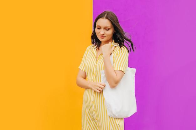 Ein mädchen im gelben kleid mit leinentragetasche in der stadt. wiederverwendbare öko-tasche.