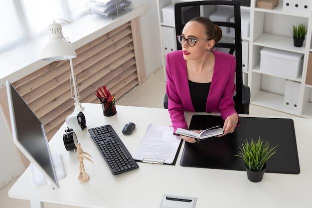 Ein mädchen im geschäftsstil arbeitet mit dokumenten im büro