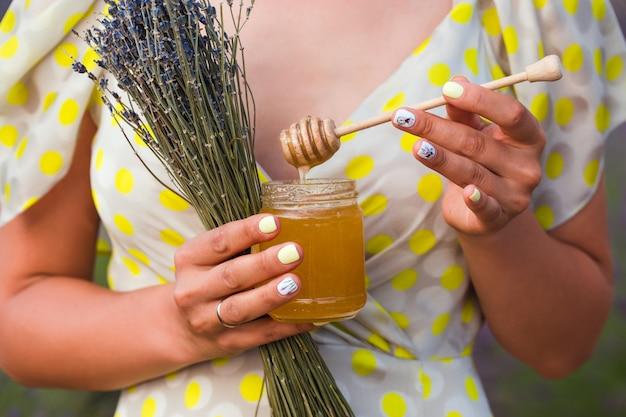 Ein mädchen im kleid steht mitten auf einem lavendelfeld. in ihren händen liegt ein strauß lavendel und ein glas honig.