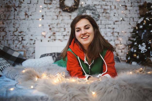 Ein mädchen im neujahrsoverall mit festlicher stimmung liegt auf einem bett um leuchtende girlanden