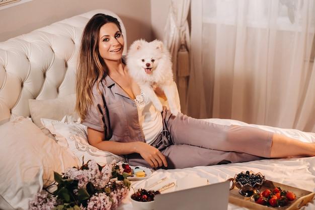 Ein mädchen im pyjama sitzt nachts im bett, während ihr weißer hund einen laptop beobachtet und süßigkeiten isst. mädchen mit einem hund spitzer zu hause im bett.