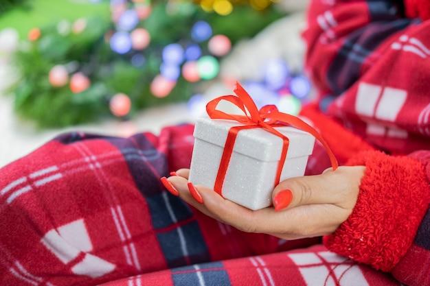 Ein mädchen im weihnachtsmann-pyjama hält eine schachtel überraschungsgeschenk