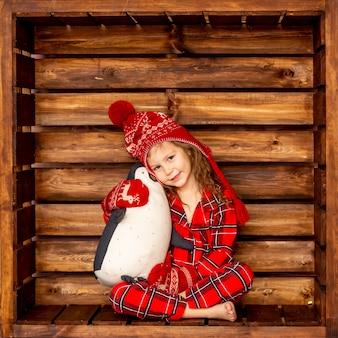 Ein mädchen im weihnachtspyjama in einem hut und fäustlingen umarmt ein ausgestopftes pinguinspielzeug auf einem hölzernen hintergrund