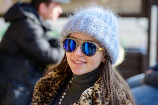 Ein mädchen in blauen gläsern und einem warmen prallen grauen hut, der draußen in der kalten jahreszeit aufwirft. porträt eines schönen mädchens in gläsern