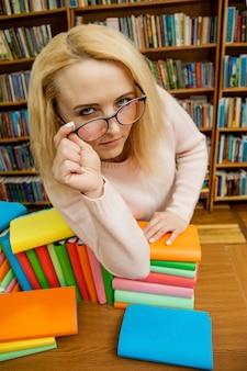 Ein mädchen in der bibliothek schaut durch die brille