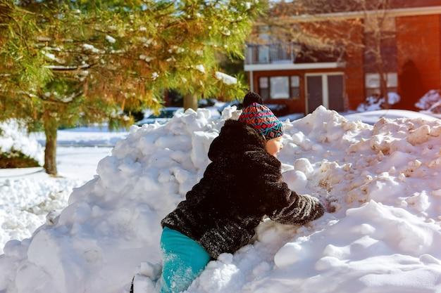 Ein mädchen in der winterkleidung läuft zu einem schneehügel mit einem spielen im winter mit schnee