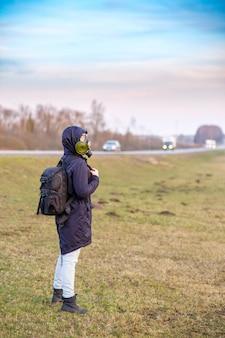 Ein mädchen in dunkler kleidung, gasmaske und kapuze auf dem kopf per anhalter