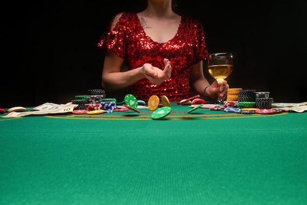 Ein mädchen in einem abendkleid spielt in einem casino und wirft croupier-chips