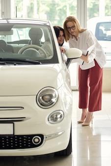 Ein mädchen in einem autohaus kauft ein kleines stadtauto.