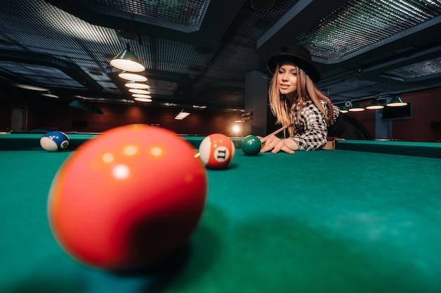 Ein mädchen in einem billardclub mit einem stichwort in den händen schlägt einen ball