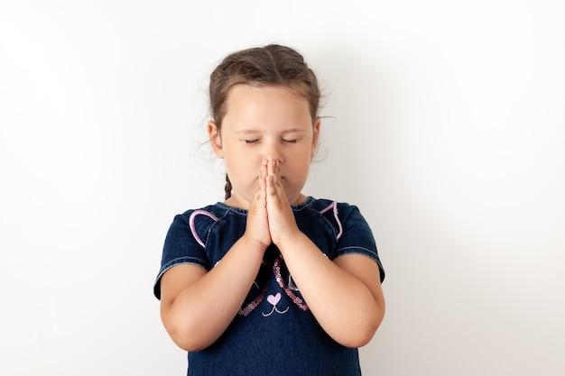 Ein mädchen in einem blauen jeanskleid verschränkt die hände vor dem gesicht, schließt die augen und betet. kind, isoliert