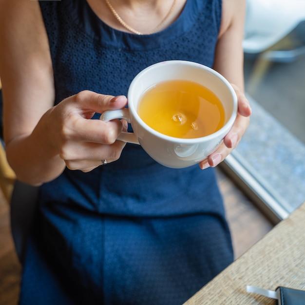 Ein mädchen in einem blauen kleid hält eine tasse tee.