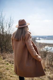 Ein mädchen in einem braunen mantel, hut und brille geht im park mit einem see unter der hellen sonne spazieren.