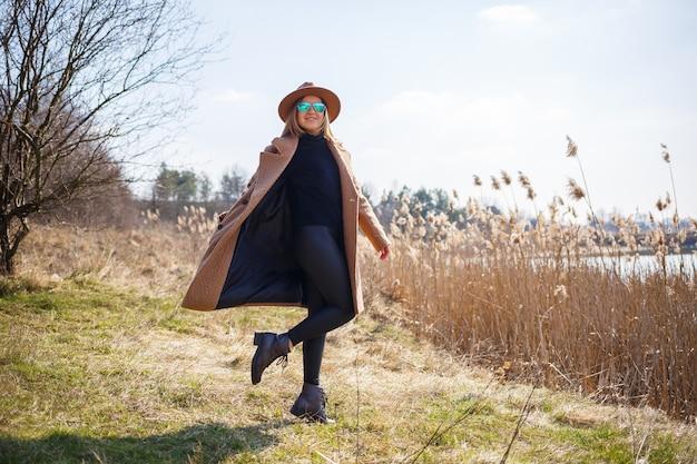Ein mädchen in einem braunen mantel, hut und brille geht in einem park mit einem see unter der hellen sonne spazieren. erfreut sich am leben und lächelt. der frühlingsanfang