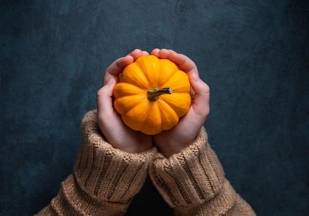 Ein mädchen in einem braunen pullover hält einen dekorativen orange kürbis in ihrer hand auf dunklem hintergrund. draufsicht, speicherplatz kopieren und schließen