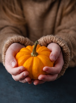 Ein mädchen in einem braunen pullover hält einen dekorativen orangefarbenen kürbis in der hand auf dunkelheit.