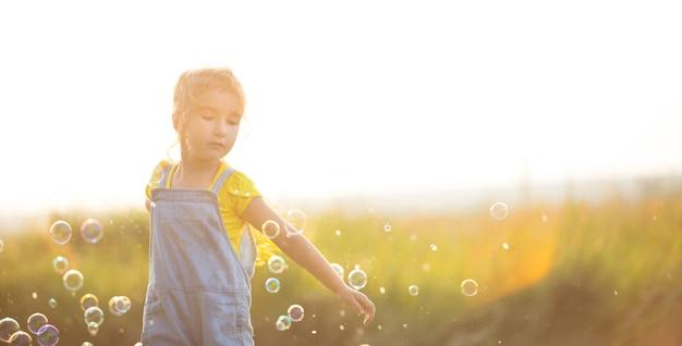 Ein mädchen in einem denim-overall bläst im sommer auf einem feld bei sonnenuntergang seifenblasen. internationaler kindertag, glückliches kind, outdoor-aktivitäten. sommer hintergrund. gesunder und umweltfreundlicher lebensstil