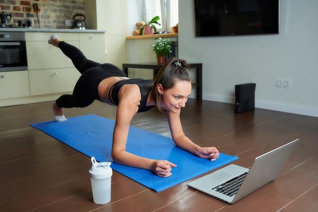 Ein mädchen in einem engen trainingsanzug trainiert das gesäß mit einem online-video auf einem laptop.