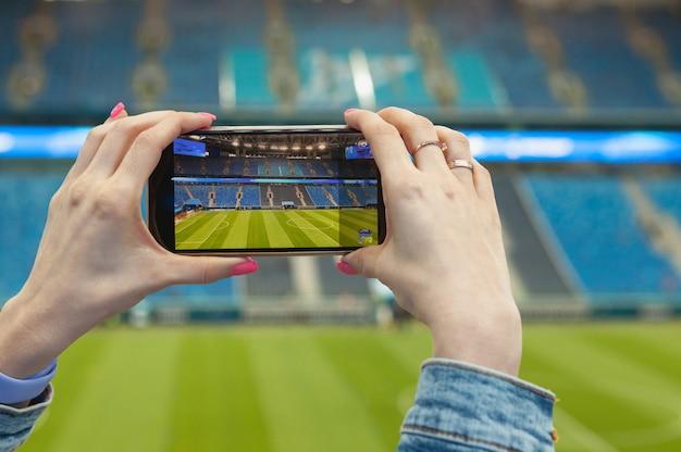 Ein mädchen in einem fußballstadion mit einem smartphone, das foto macht