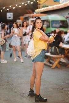 Ein mädchen in einem gelben hemd, shorts und schwarzen schuhen mit einem netz aus zitronen und zitronensaft geht eine stadtstraße entlang. eine frau mit einem cocktail in den händen.