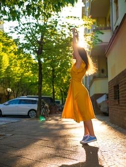 Ein mädchen in einem gelben sommerkleid geht in den sonnenstrahlen die straße entlang.