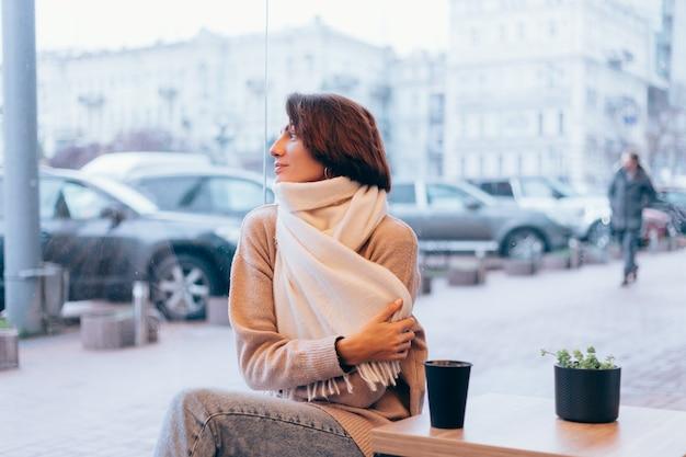 Ein mädchen in einem gemütlichen café wärmt sich mit einer tasse heißen kaffees auf