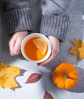 Ein mädchen in einem grauen pullover hält eine tasse tee mit zitrone in der hand auf grau