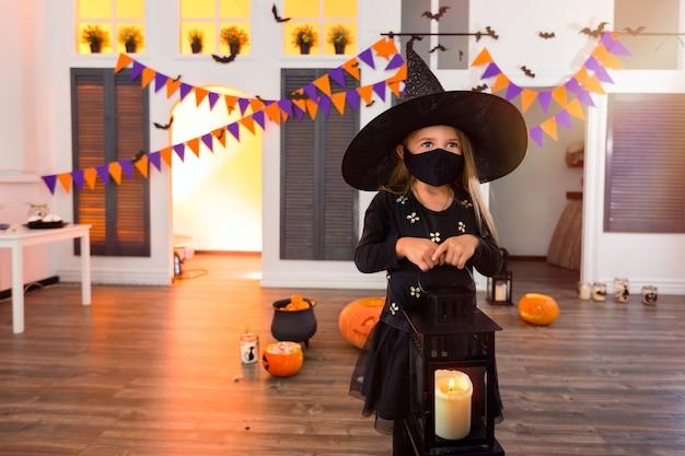 Ein mädchen in einem halloween-kostüm mit einer maske hält eine laterne mit einer kerze bei einem herbstfest