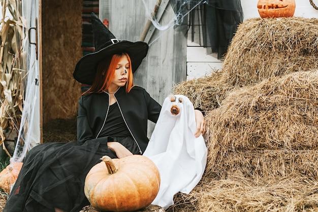 Ein mädchen in einem hexenkostüm mit einem hund in einem geisterkostüm hat spaß auf der veranda eines hauses, das dekoriert ist, um eine halloween-party zu feiern