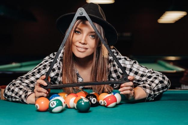 Ein mädchen in einem hut in einem billardclub mit bällen in den händen. billard spielen.