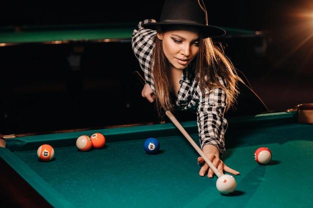 Ein mädchen in einem hut in einem billardclub mit einem stichwort in den händen schlägt einen ball. billard spielen.