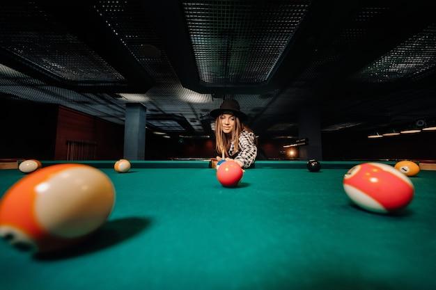 Ein mädchen in einem hut in einem billardclub mit einem stichwort in den händen schlägt einen ball.