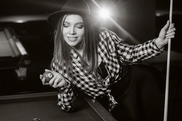 Ein mädchen in einem hut in einem billardclub mit einem stichwort und bällen in ihren händen. schwarzweiss-foto.