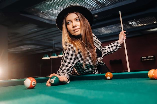 Ein mädchen in einem hut in einem billardclub mit einem stichwort und bällen in ihren händen.