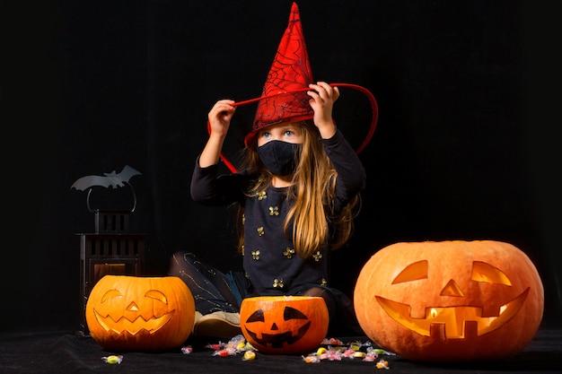 Ein mädchen in einem karnevalskostüm der hexe und einer medizinischen maske auf spielen mit kürbissen und süßigkeiten