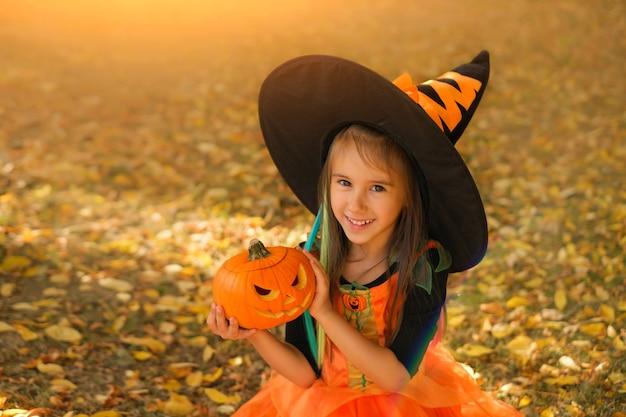 Ein mädchen in einem kostüm und einem hexenhut hält einen halloween-kürbis