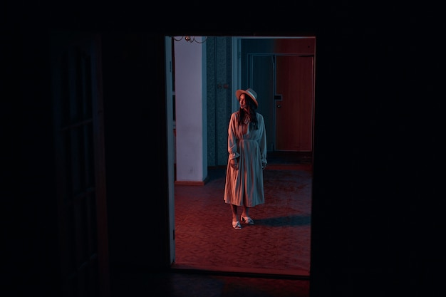 Ein mädchen in einem langen chiffonkleid und hut steht in einem dunklen raum. kreatives shooting mit roter neonbeleuchtung. foto in hoher qualität