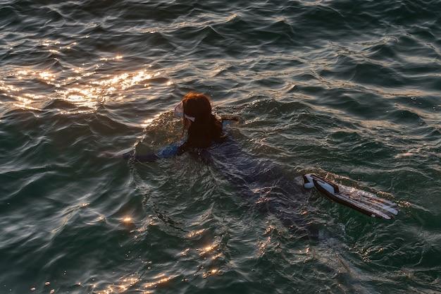 Ein mädchen in einem neoprenanzug schnorchelt im meer