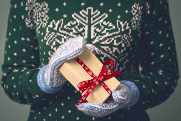 Ein mädchen in einem neujahrspullover hält ein geschenk. geschenke für männer. fröhliche weihnachten. geschenk für ein mädchen. pullover mit weihnachtsverzierung. strickkleid.