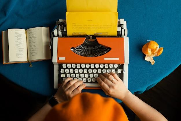 Ein mädchen in einem orangefarbenen barett tippt auf einer orangefarbenen schreibmaschine, liest gedichte und isst eine mandarine